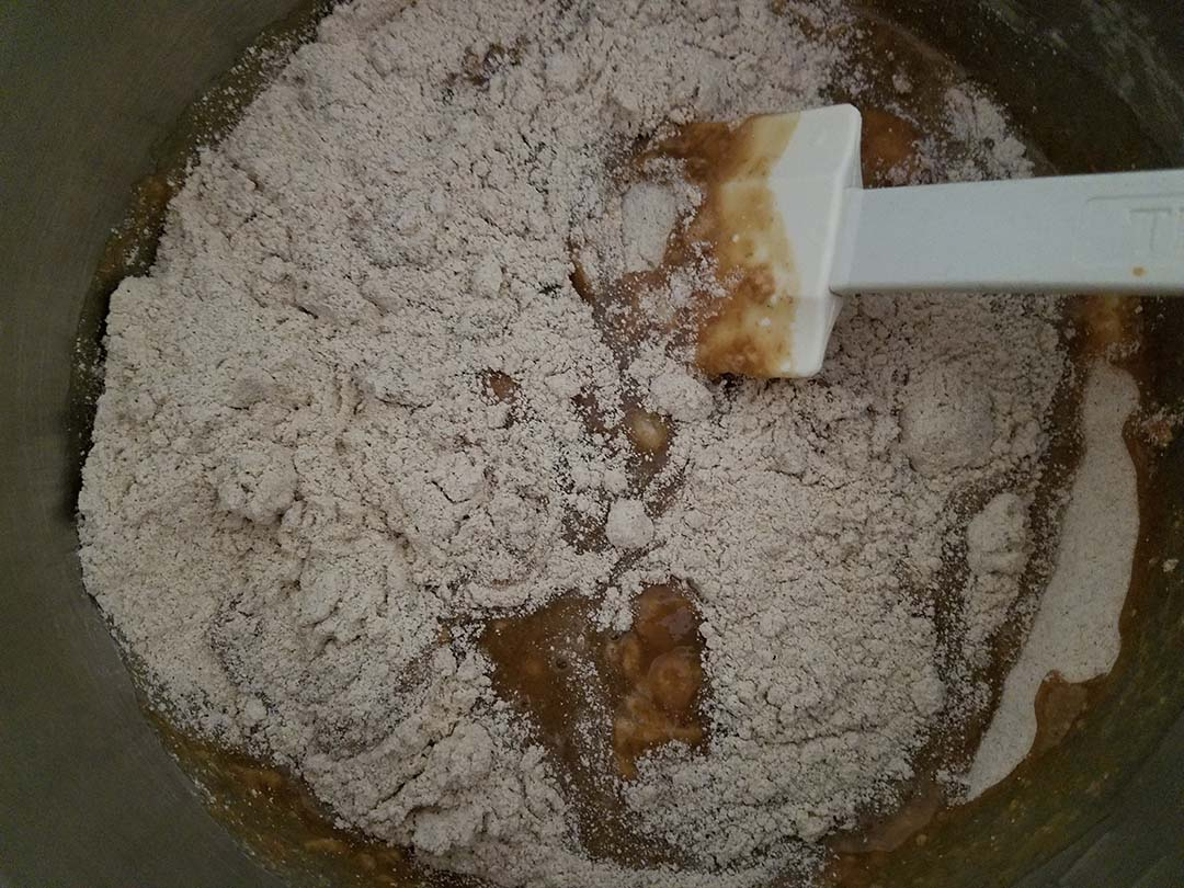 mixing banana mixture with flour for banana bread